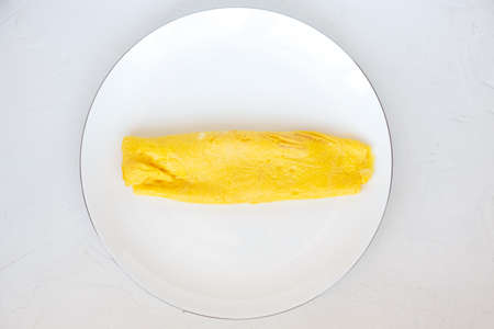 Simple french egg omelette on white background.