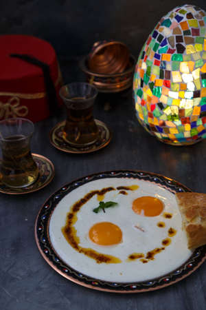 Cilbir, eggs in yogurt with spiced butter and herbs, served with bread and tea, turkish cuisine, copy space