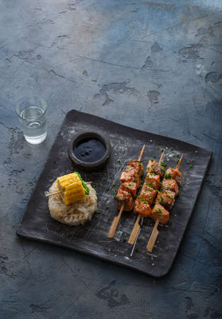 Salmon skewers with noodles and corn, copy space. Stock Photo