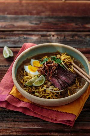 Malay mee rebus with beef, eg and onion in a bowl, copy space Banco de Imagens