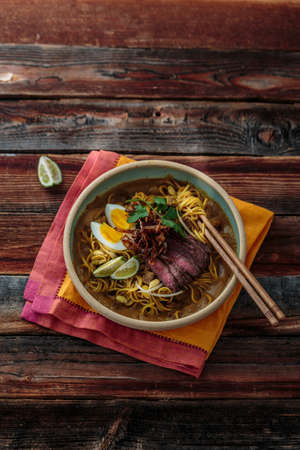 Malay mee rebus with beef, eg and onion in a bowl, copy space Stock Photo