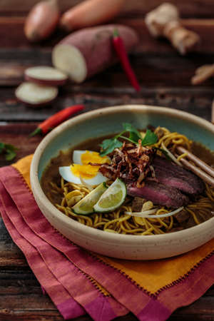 Bowl of spicy mee rebus with chopsticks, malaysian cuisine Stock Photo