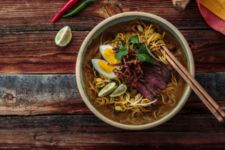 Boiled noodles, beef steak, egg, onion in a bowl, asian cuisine, copy space. Stock Photo