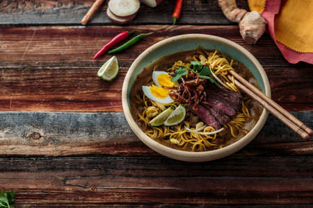 Bowl of noodles with egg, beef and onion