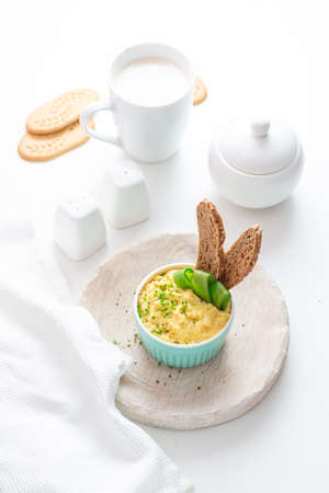 Scrambled eggs with chives and bread, white background.