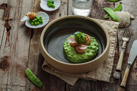 Scallops with pea puree on wooden background, rustic style