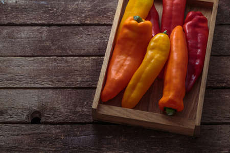 Ripe Colorful Peppers on Wooden background, copy space.