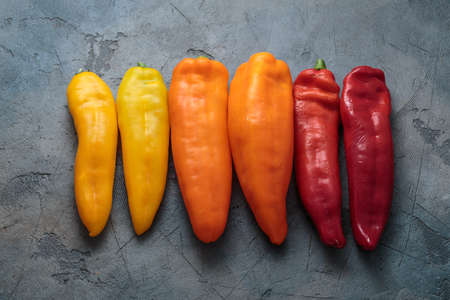 Box of ripe color peppers on wooden background.