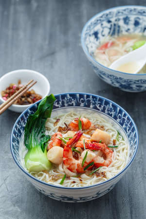 Seafood noodle soup or singaporean bee hoon in traditional bowl 写真素材