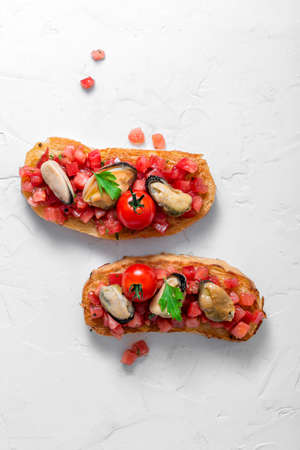 Smoked mussels on grilled bruschetta with tomatoes, white background, isolated 写真素材