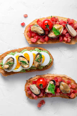 Crusty bread with smoked mussels on griloled bread with tomatoes, top view 写真素材