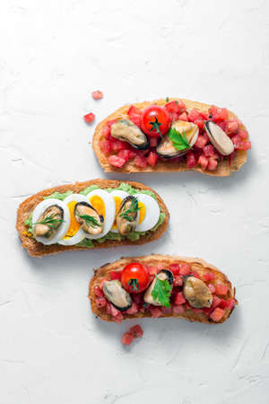Tapas with smoked mussels on griloled bread with tomatoes and avocado, top view