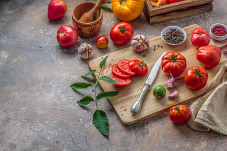 Raw tomatoes on cutting board with knife, copy space