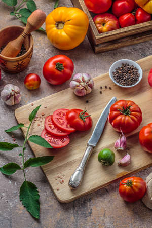Tomatoes on cutting board with knife, top view