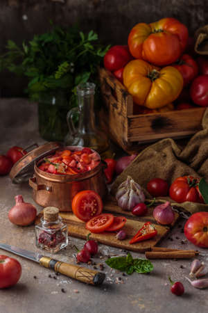 Chopped tomatoes in a copper pan with ripe tomatoes on background