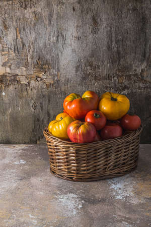 Ripe heirloom tomatoes in the basket, copy space