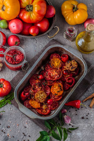 Baked tomatoes in a metal tray with ripe tomatoes on background, top view Zdjęcie Seryjne