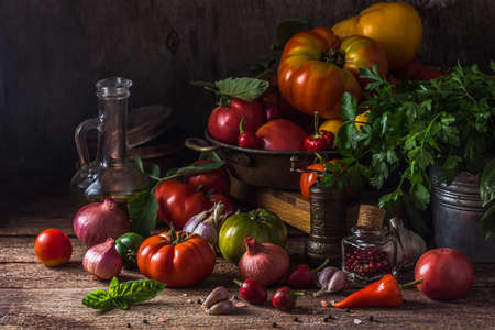 Ripe tomatoes with chili, onion and olive oil on a rustic table