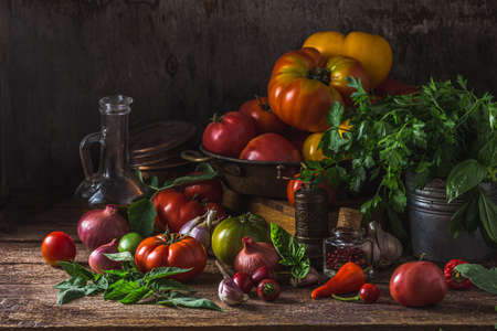 Assorted tomatoes on dark rustic table, copy space