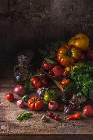 Ripe tomatoes on dark rustic table, copy space