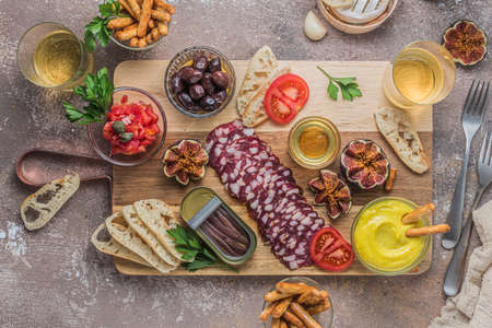 Salami, cheese, anchoves, bread and alioli dip on wooden board, flat lay Zdjęcie Seryjne
