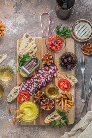 Wine snacks set. Sausage, olives, tomatoes, baguette slices, camembert cheese on wooden board