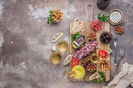 Typical spanish tapas concept. Salami, cheese, bowls with olives, tomatoes and alioli dip. Copyspace Stok Fotoğraf - 129798948