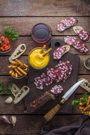 Cured sausage and crusty bread with red wine, top view Stockfoto - 129798954