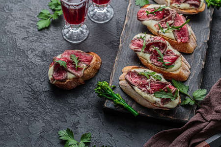 Bruschetta with roast beef, mayo and greens leaves on wooden board.