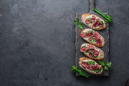 Crostini with roast beef on black board, copy space flat lay Banco de Imagens