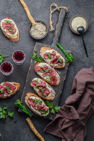Bruschettas with beef on wooden board, copy space Banco de Imagens