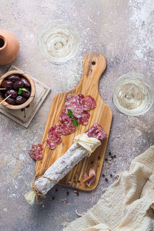 Italian salami on wooden board with cheese and olives, copy space