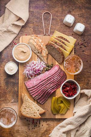 Sliced Deli Pastrami on wooden board, flat lay