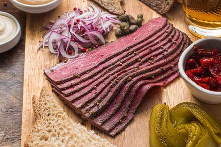 Sliced Deli Pastrami on wooden board, flat lay. Stock Photo