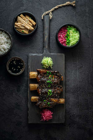 Braise beef short ribs, asian style with rice and radish, dark photo, flat lay