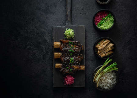 Braise beef short ribs, asian style with rice and radish, dark photo, copy space Banque d'images