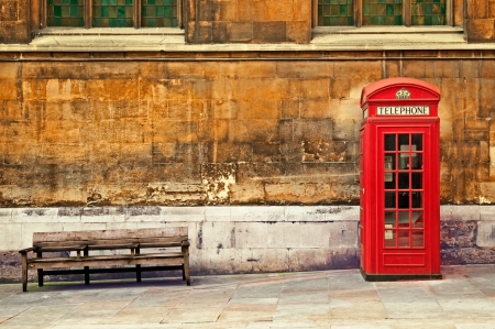 street scene: Traditional old style UK red phone box in London.