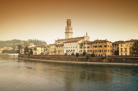 アディジェ川と川岸のアパートのビュー。ヴェローナ大聖堂とカステル サン ピエトロも表示されます。