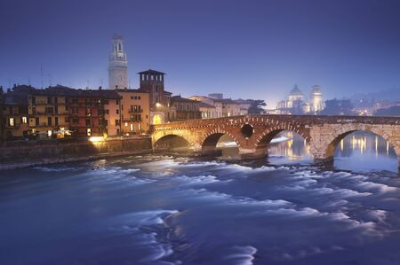 Ponte Pietra and the River Adige at a foggy evening. photo