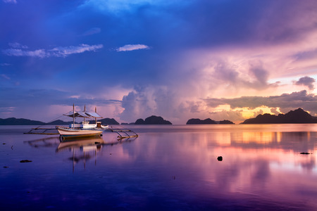 Tropical sunset with a banca boat in El Nido, Palawan - Philippines