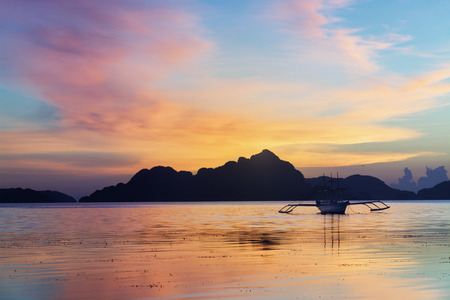 Tropical sunset with a banca boat in El Nido, Palawan - Philippines photo