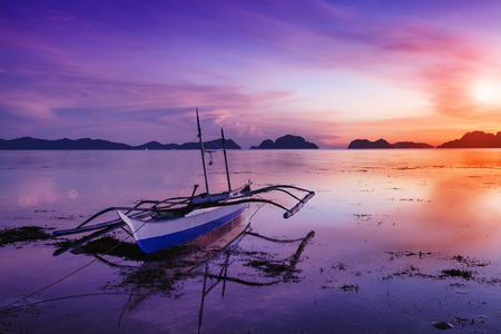 Tropical sunset with a banca boat in Palawan - Philippines photo