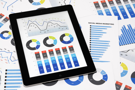 Business graph: Business charts and diagrams on digital tablet.
