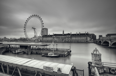 december 25th: London, England - December 25th, 2010: Gloomy, Black and White image of the Shouth Bank of River Thames. This view including: London Eye, County Hall and Westminster Millennium Pier.