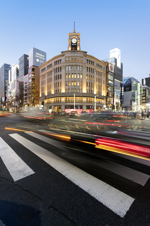 retail place: Tokyo, Japan - January 18, 2015:  Ginza shopping district at rush hour in Tokyo. The iconic Ginza Wako building is at the background.
