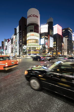 stereotypically: Tokyo, Japan - January 18, 2015:  Ginza shopping district at rush hour in Tokyo. The iconic  Sanaa Building  is at the background.