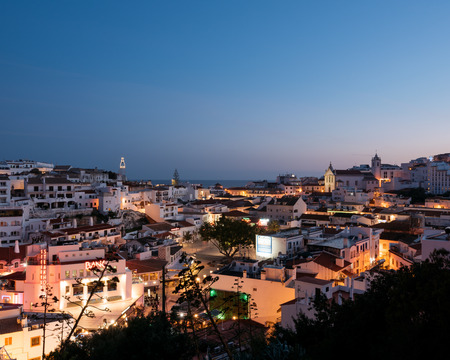 Albufeira, Portugal - April 16: Panoramic, night view of the Old Town of Albufeira City in Algarve, Portugal. Albufeira is a coastal city in the southern Algarve region of Portugal. It's a former fishing village that has become a major holiday destinati Editorial