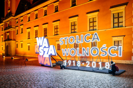 Warsaw, Poland - October 30, 2018: Tourists taking a selfie at a Warsaw - the capital of freedom Neon Sing installation in the Old of Warsaw.  Poland celebrating one hundred year anniversary of independence on 11th of November 2018.