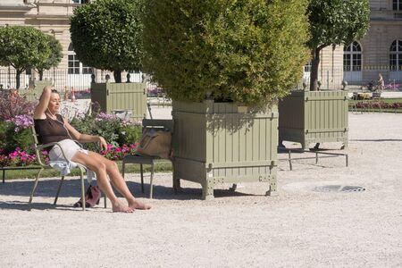Paris, France - Sept 04, 2019: A woman enjoy sunny day in the Luxembourg Garden in Paris. Luxembourg Palace is the official residence of the French Senate.