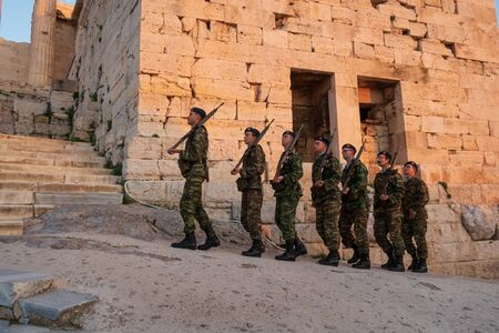 Athens, Greece - Dec 20, 2019: Greek soldiers march in formation while on patrol at the Acropolis of Athens.  Soldiers go to Acropolis to lower a Greek flag every evening.